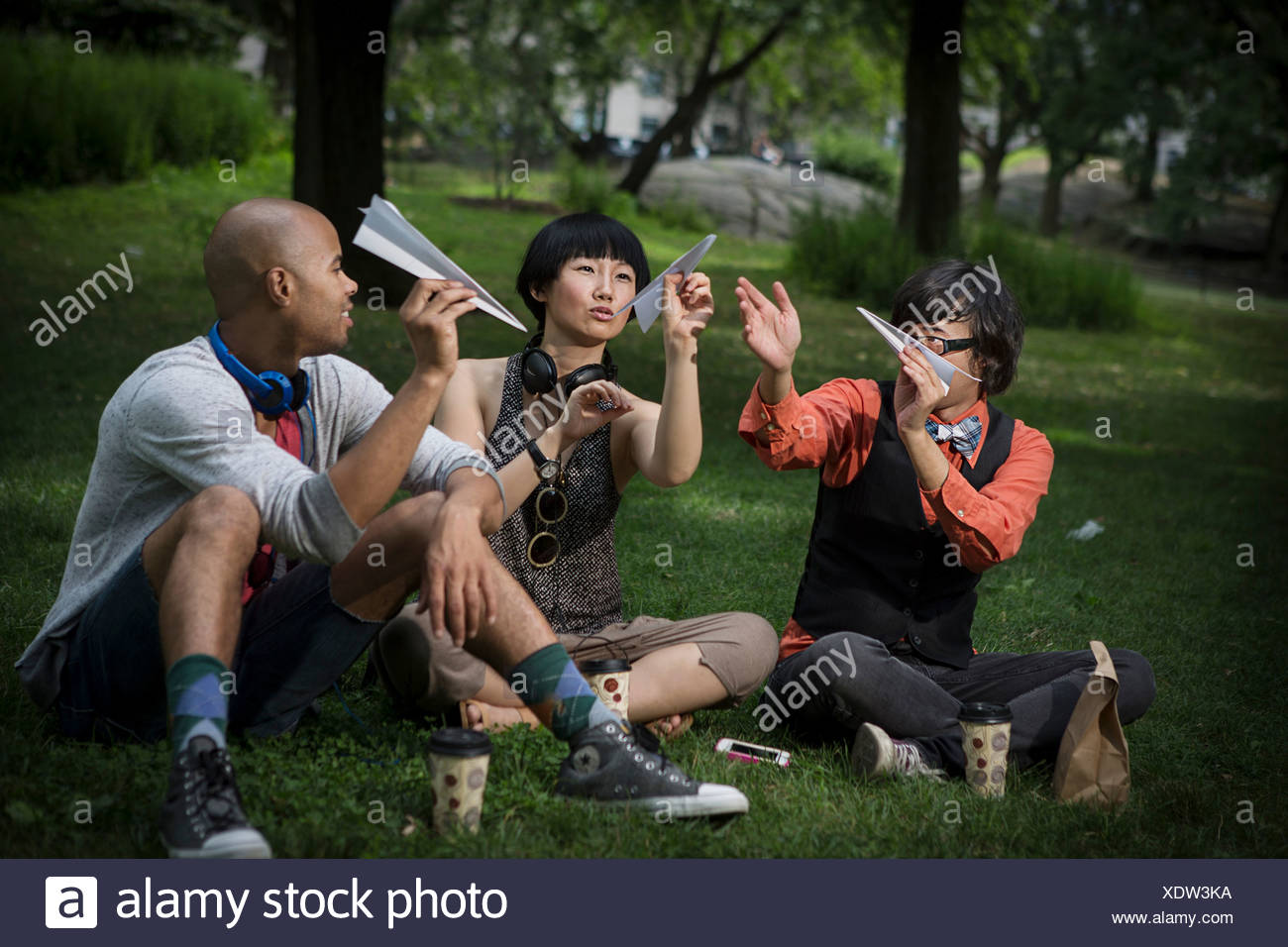 Three friends holding paper planes in park Stock Photo