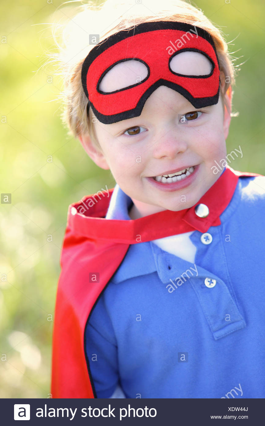 Young Boy Playing Outdoors With A Cape And A Mask; Portland, Oregon, Usa - Stock Image