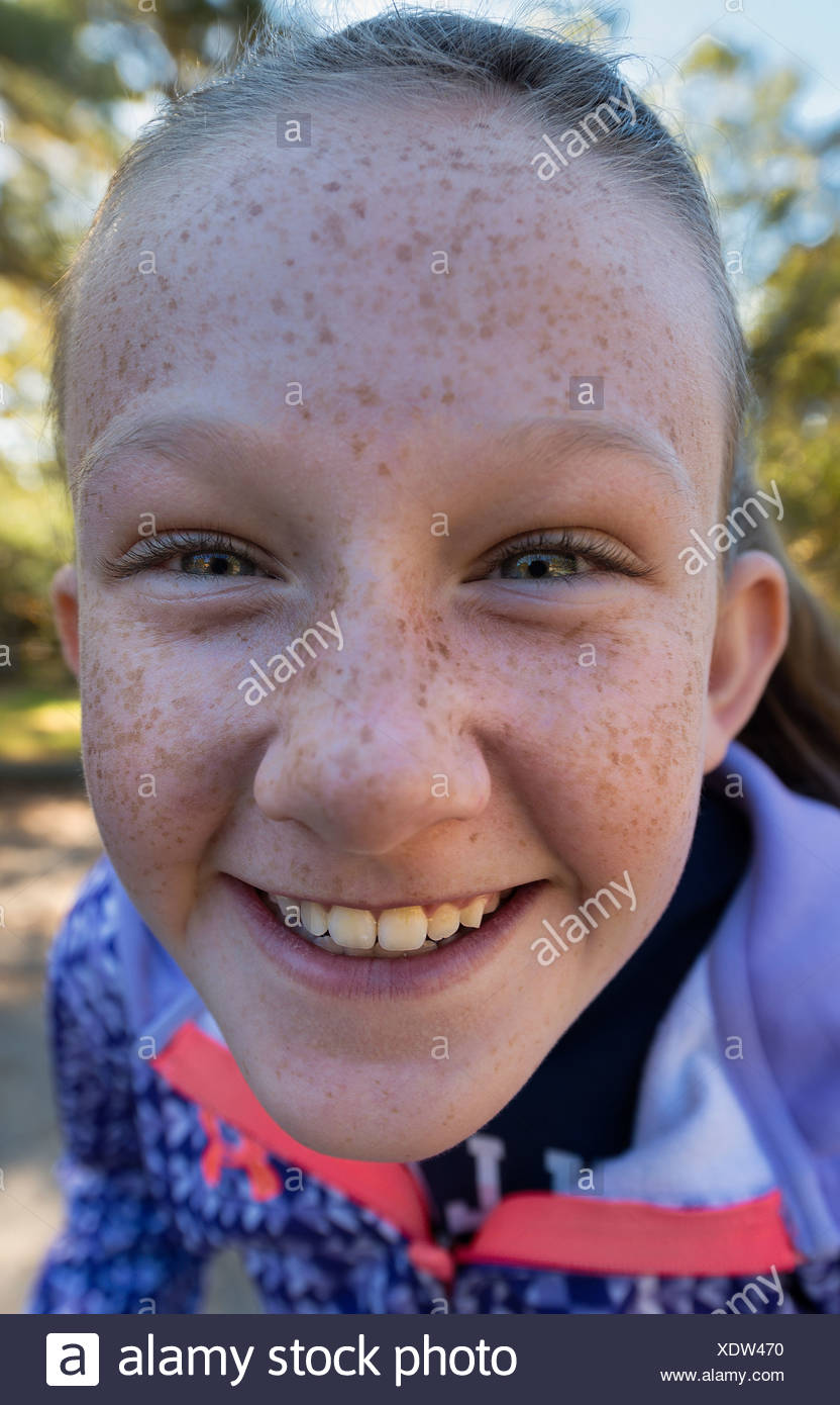 Smiling tween girl poses for a selfie. - Stock Image