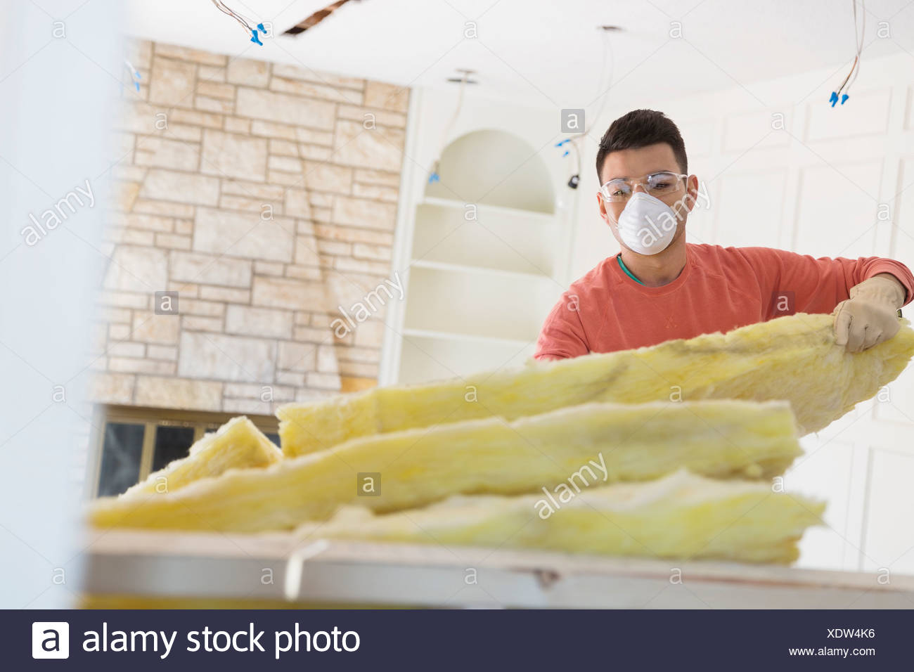 Young man installing insulation at home - Stock Image
