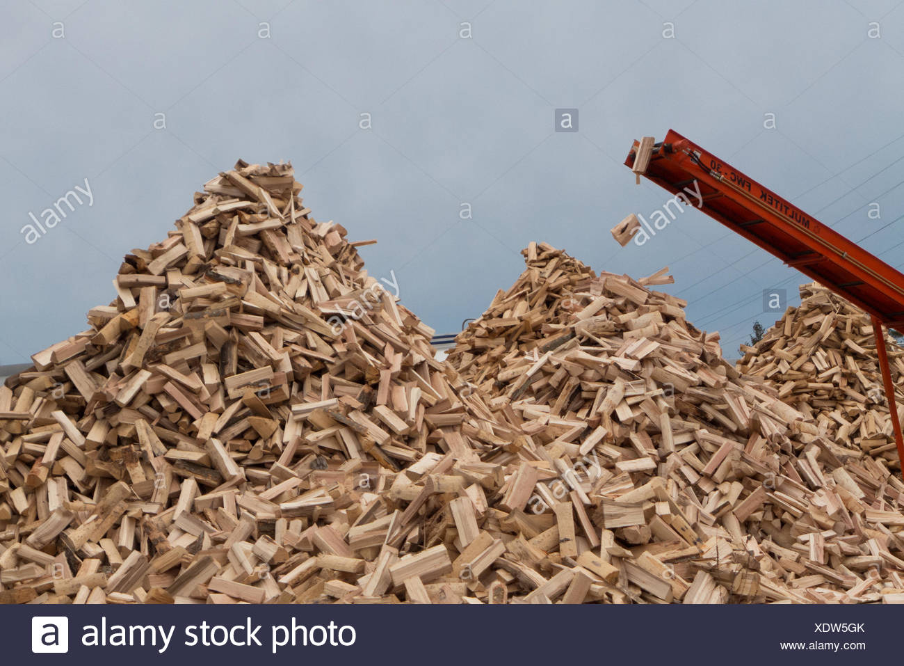 Wood is dropped from a conveyor belt onto a large firewood pile. - Stock Image