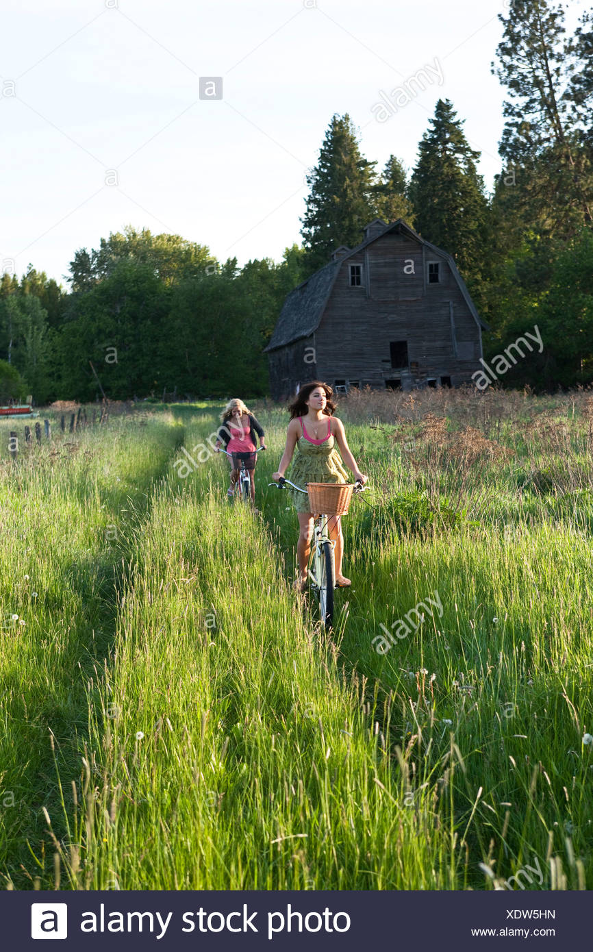 Women ride beach cruisers down a grassy path in Idaho. - Stock Image