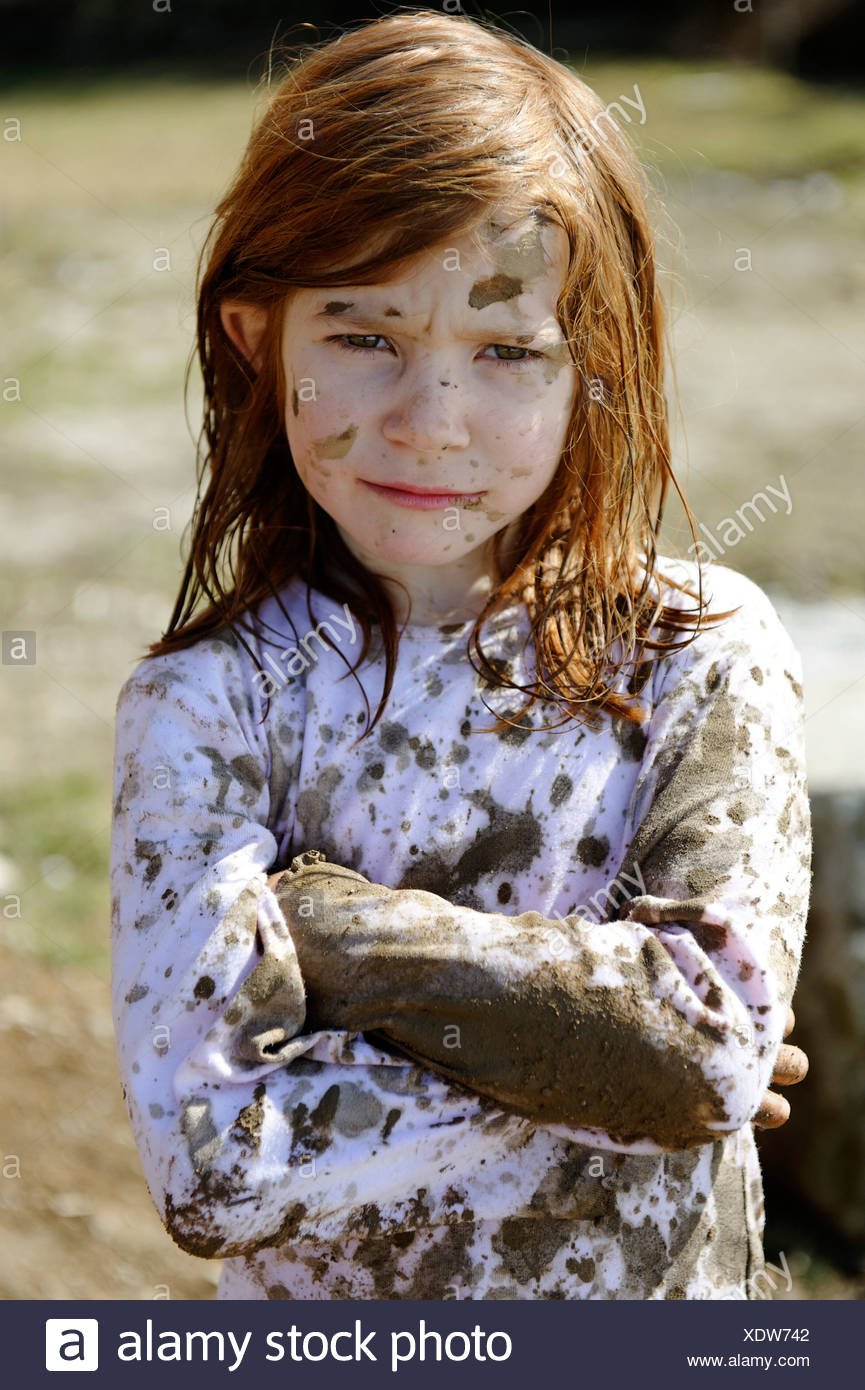 Child totally covered in mud, dirty, wild, untypical girl - Stock Image