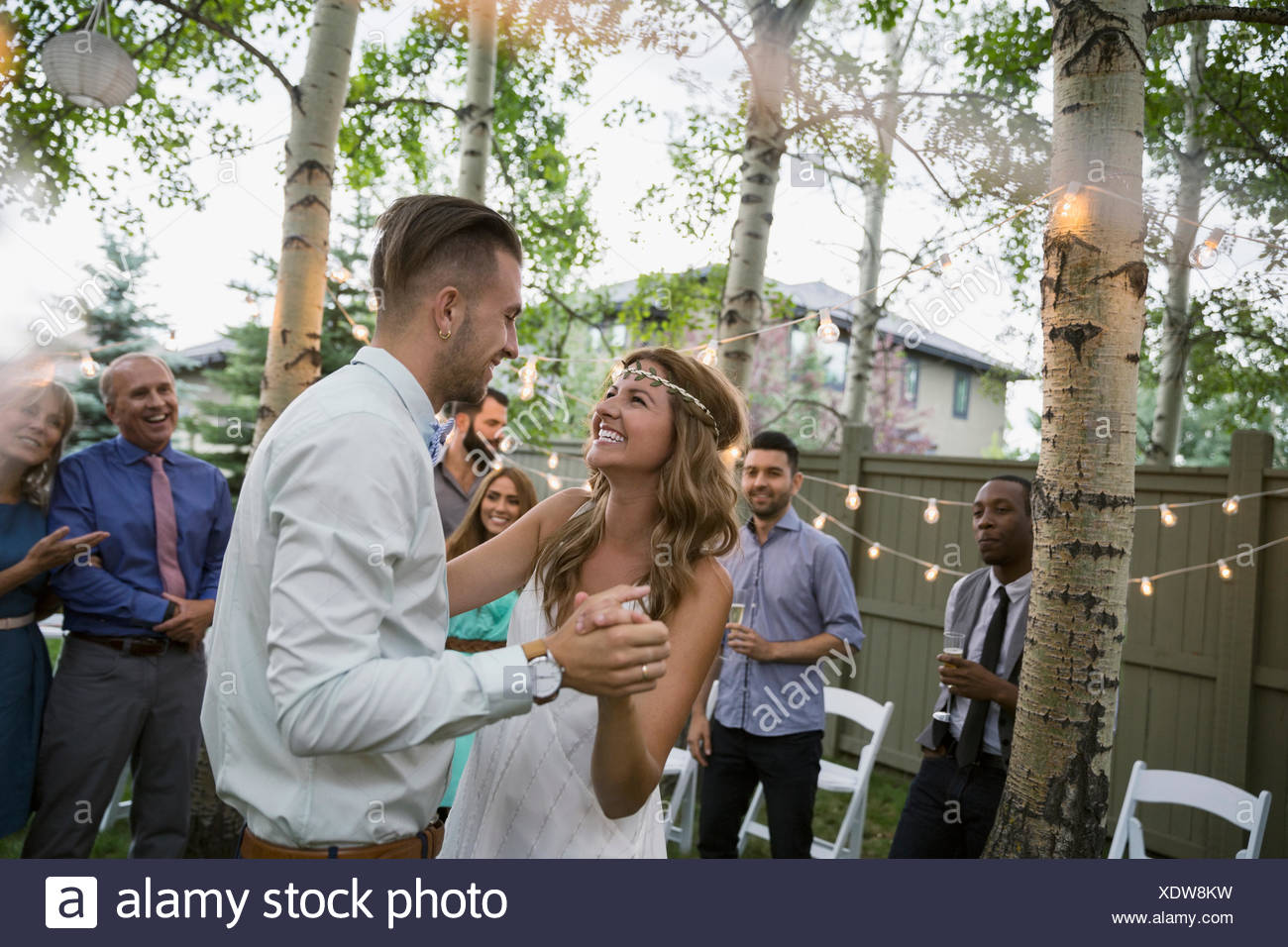 Bride and groom dancing at backyard wedding reception - Stock Image