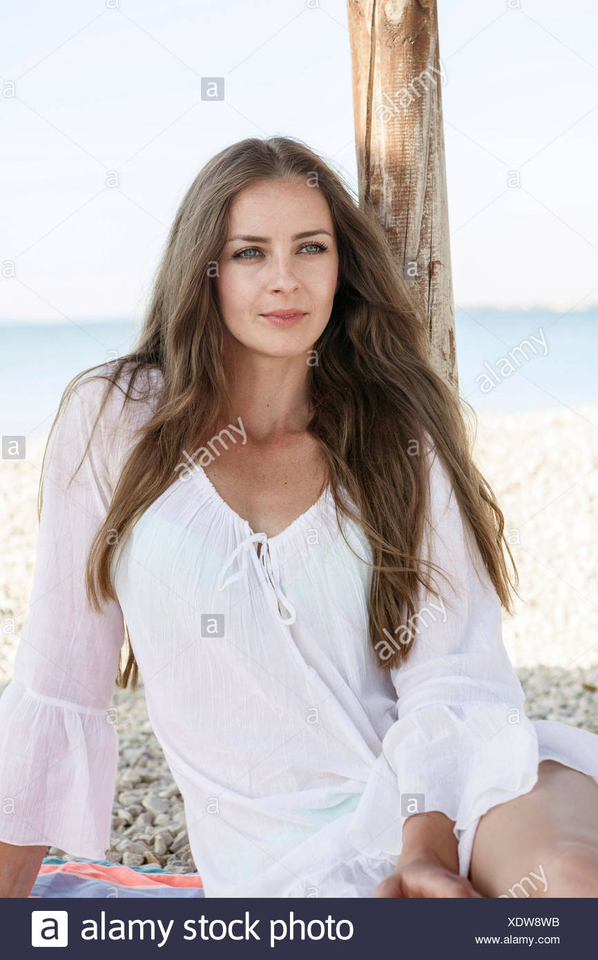 Portrait of woman with long hair on beach - Stock Image