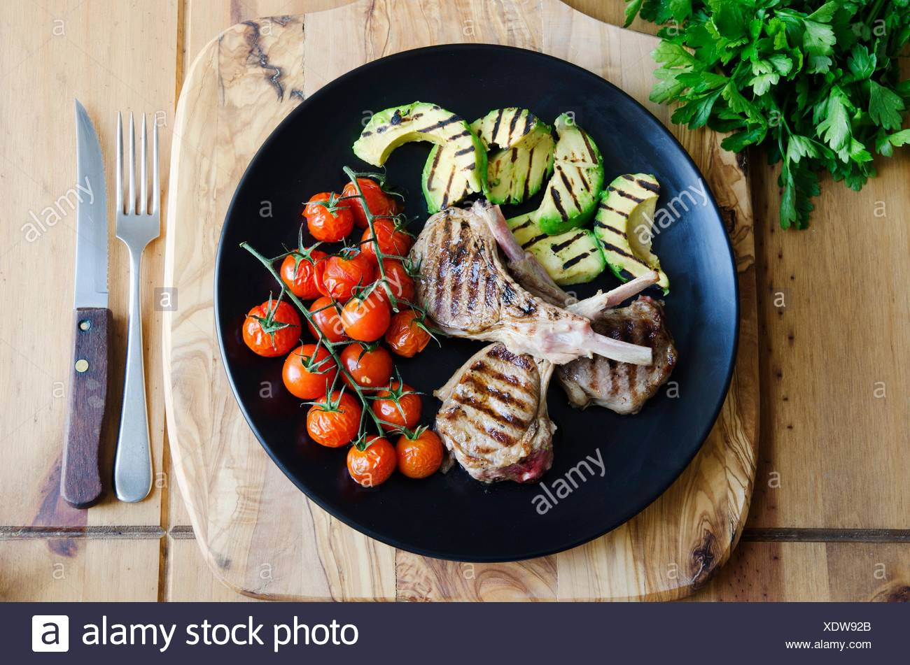 Griddled lamb cutlets with avocado and cherry tomatoes. Stock Photo