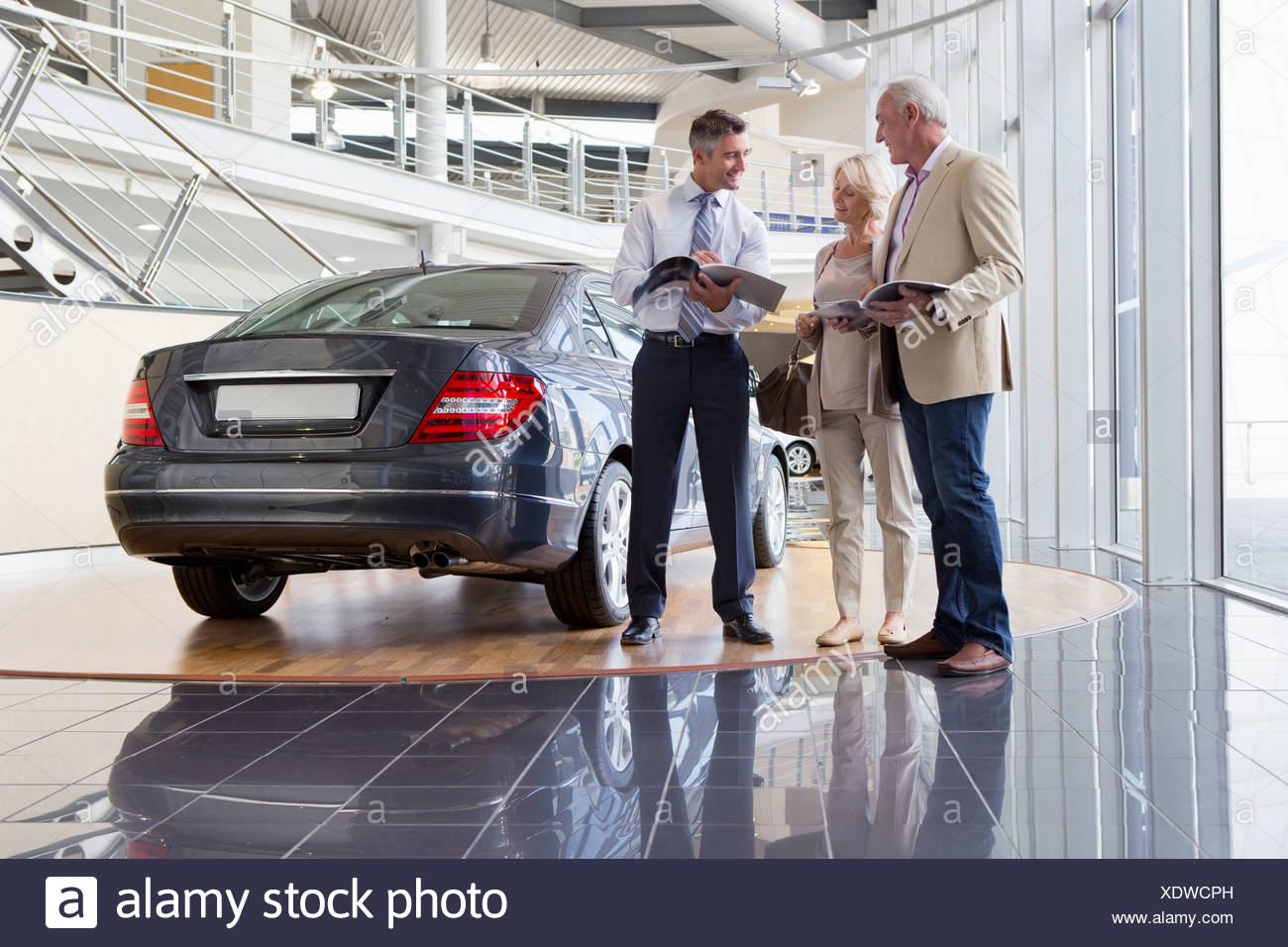 Salesman and couple with brochures next to car in car dealership showroom - Stock Image