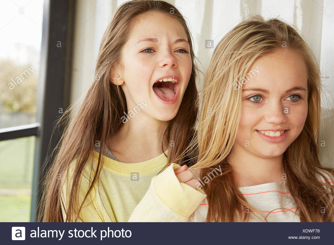 Two girls smiling and shouting from shelter - Stock Image