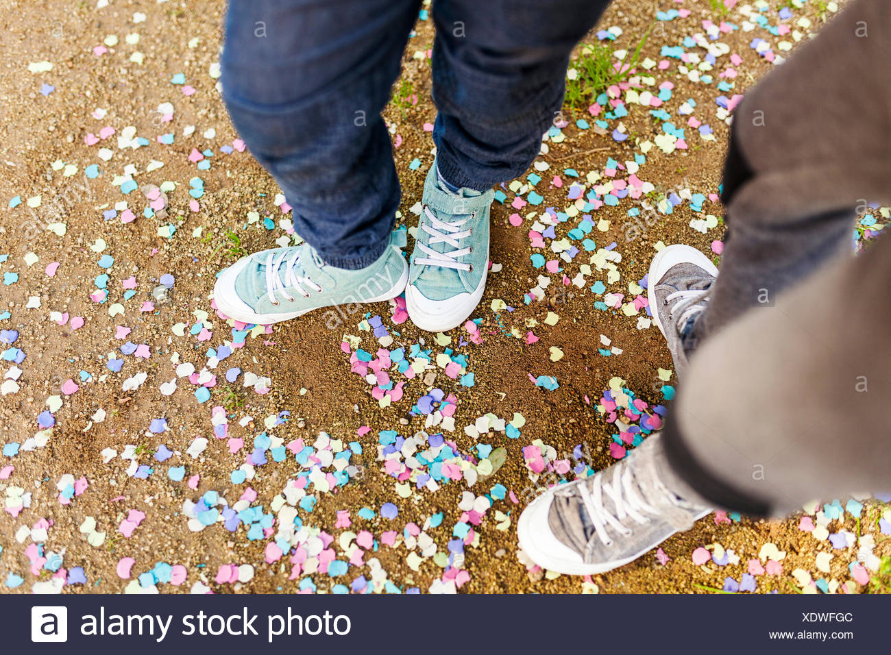 Kids standing on groung full of confetti, wearing sneakers - Stock Image