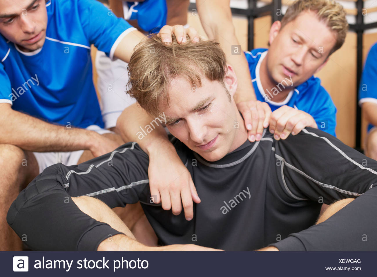 Footballers consoling team mate - Stock Image