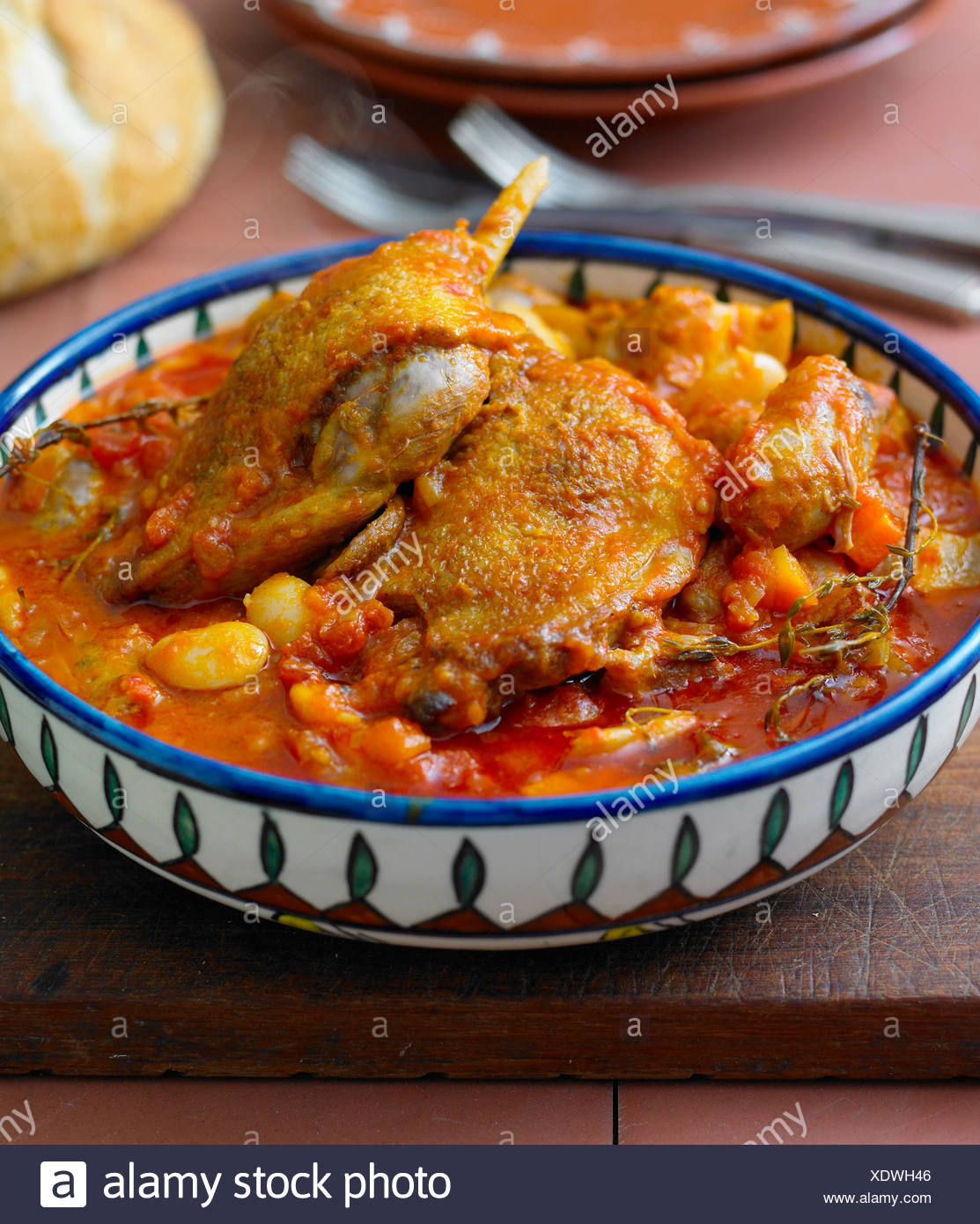 Duck Cassoulet, in colourful dish, on a chopping board - with recipe - Stock Image