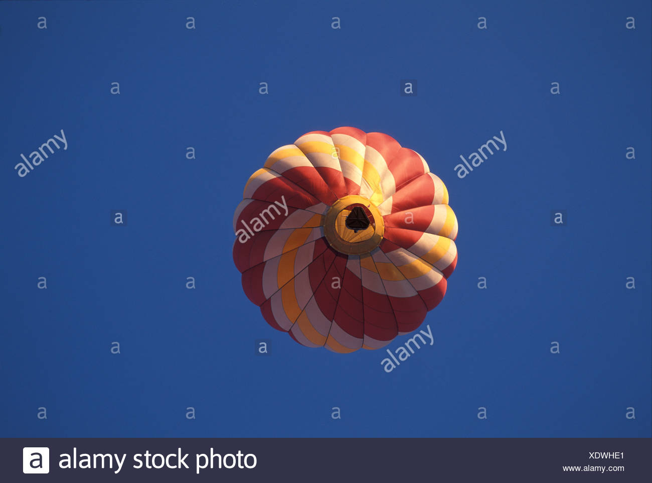 Red and yellow hot-air baloon in the blue sky - Stock Image