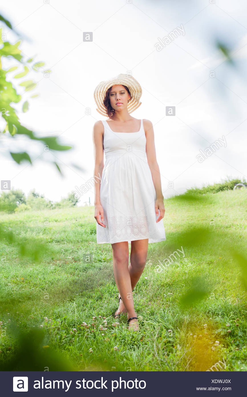 Portrait of young woman in sundress and hat walking in park - Stock Image