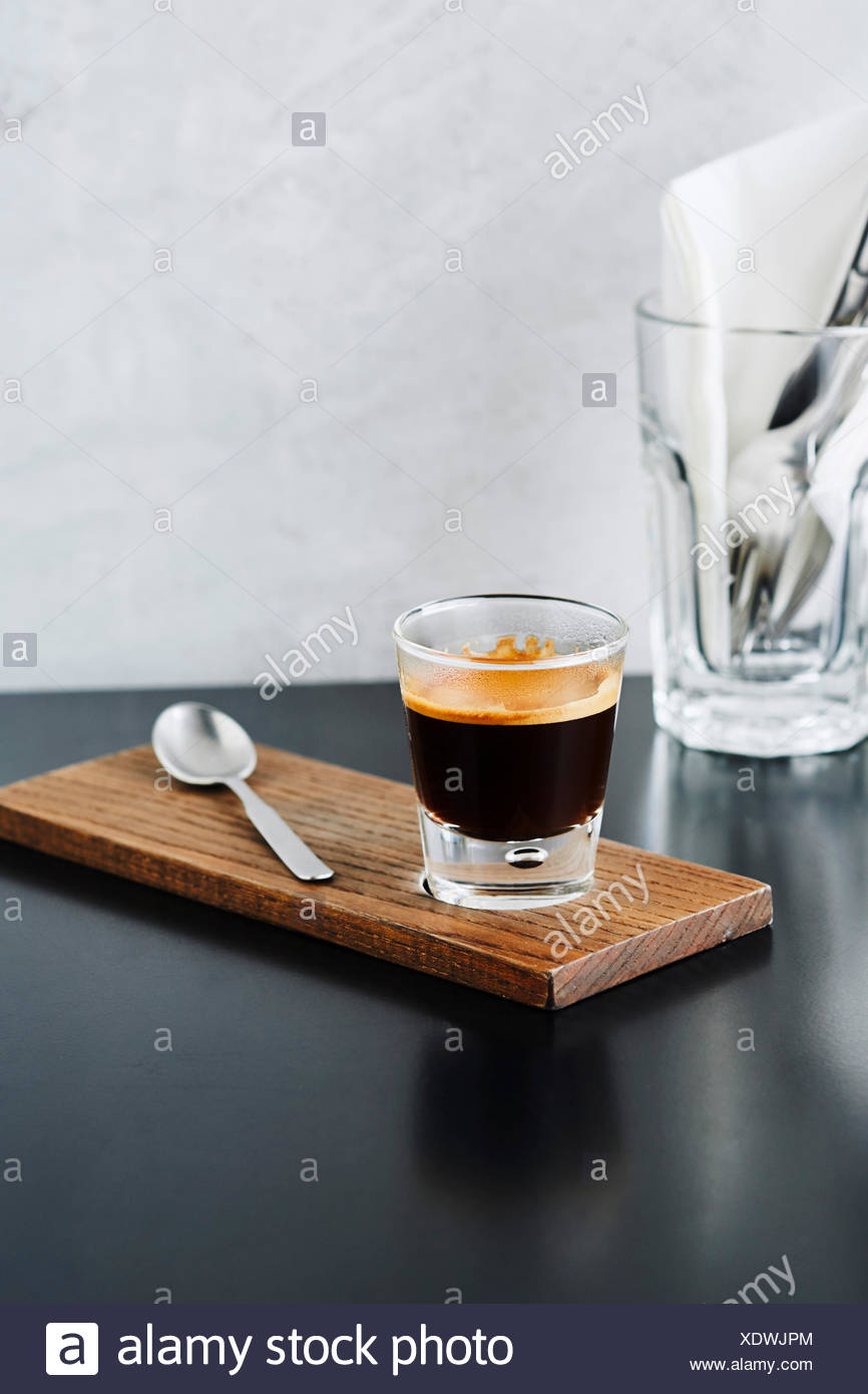 Close-up of a shot of espresso on wood board - Stock Image