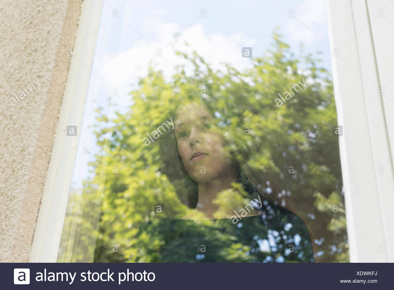 A girl looking out a window - Stock Image
