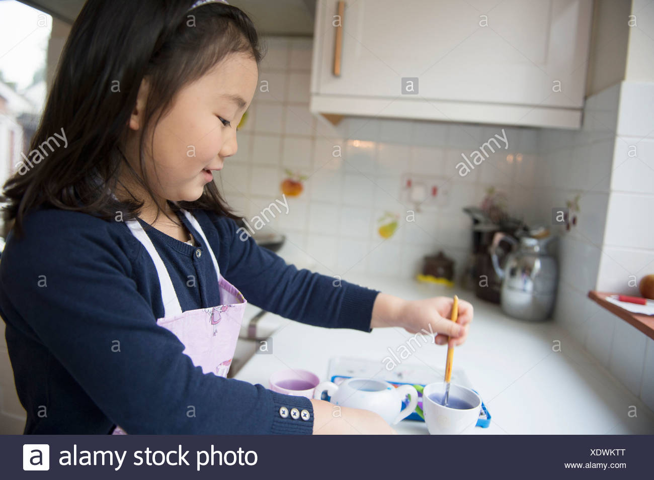 Young girl dipping paintbrush in water bowl in kitchen - Stock Image