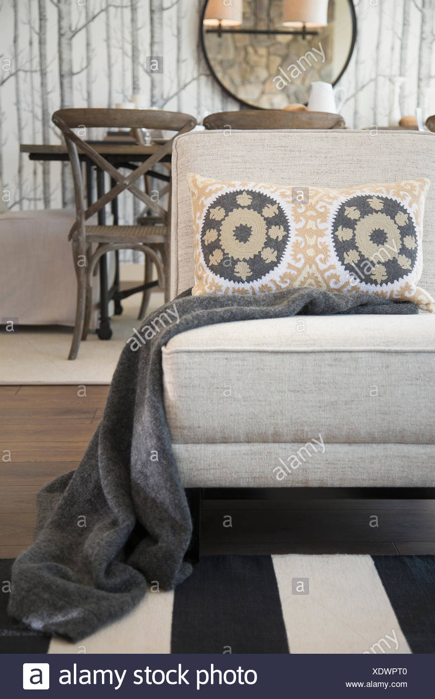 Blanket and patterned pillow on living room chair - Stock Image