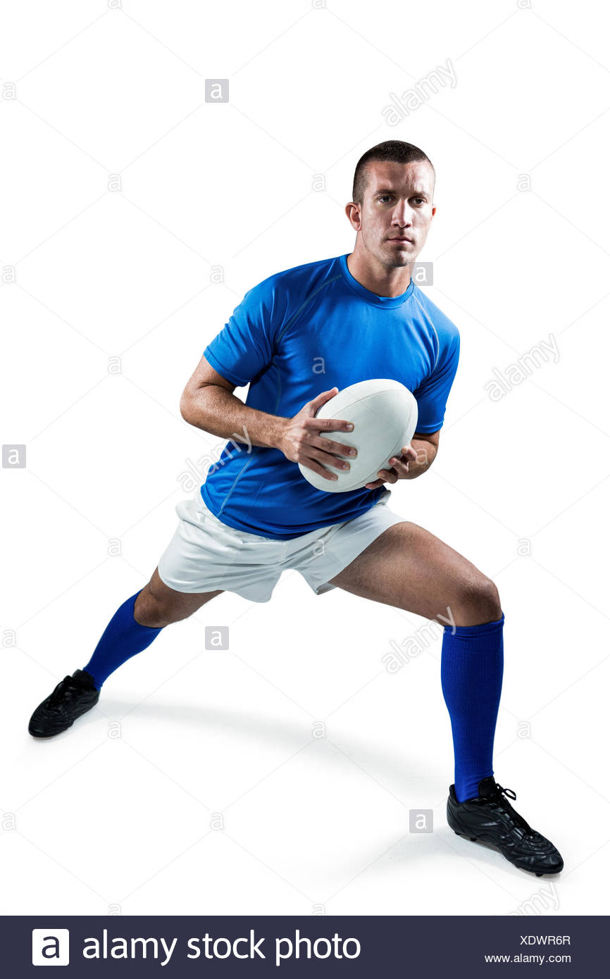 Full length of rugby player exercising with ball - Stock Image