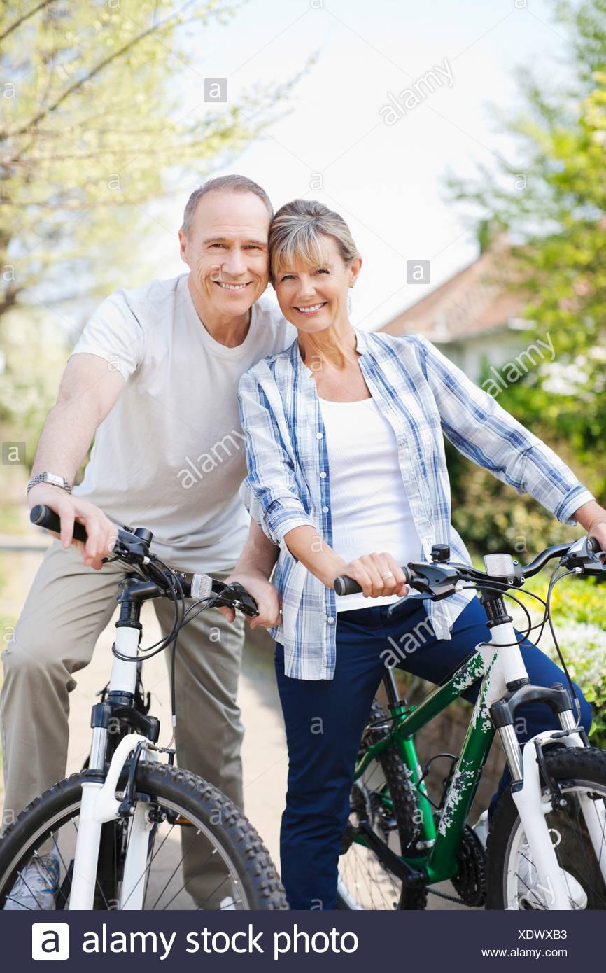 Portrait of smiling senior couple on bicycles - Stock Image