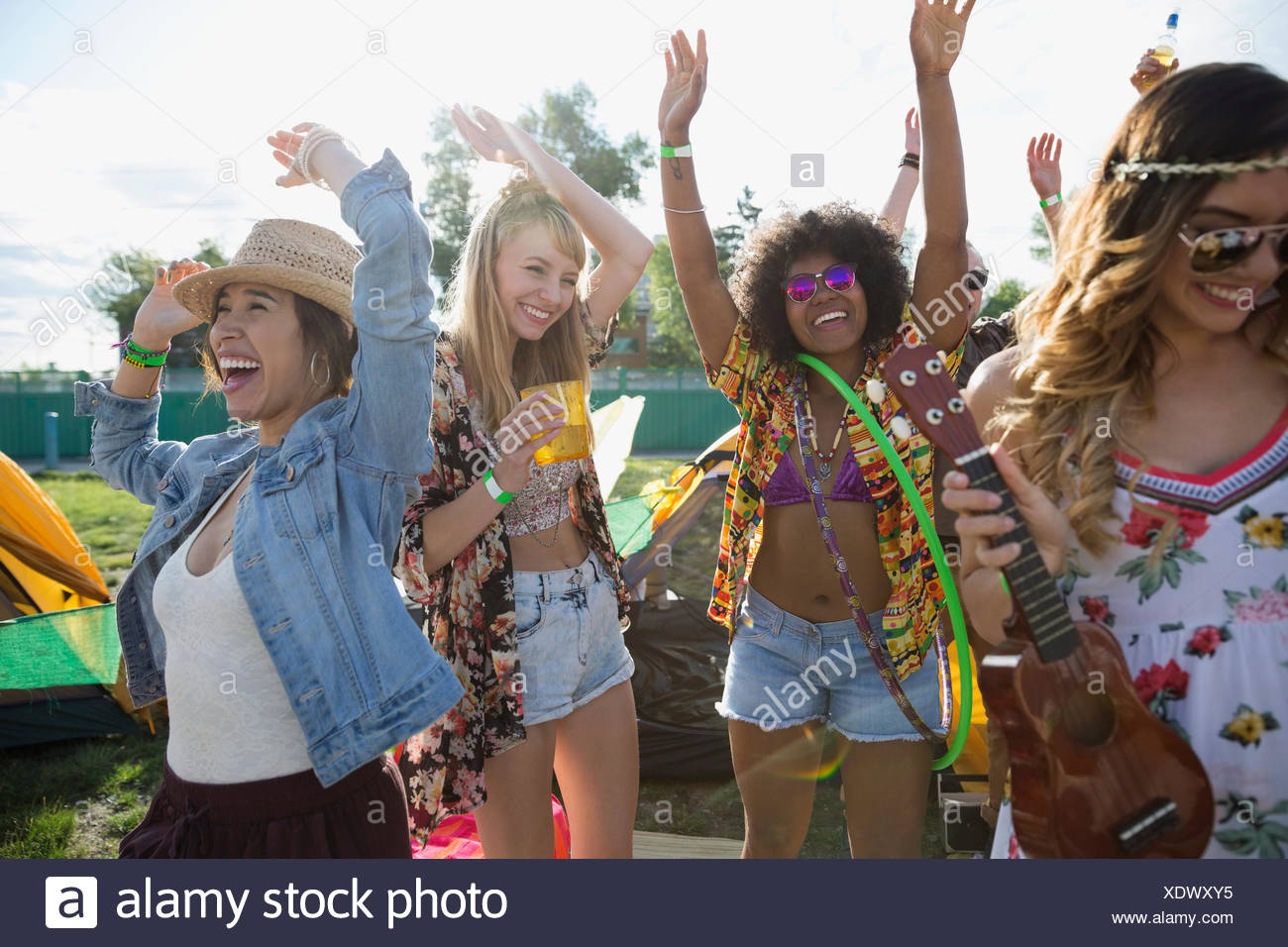 Enthusiastic young women dancing at summer music festival - Stock Image