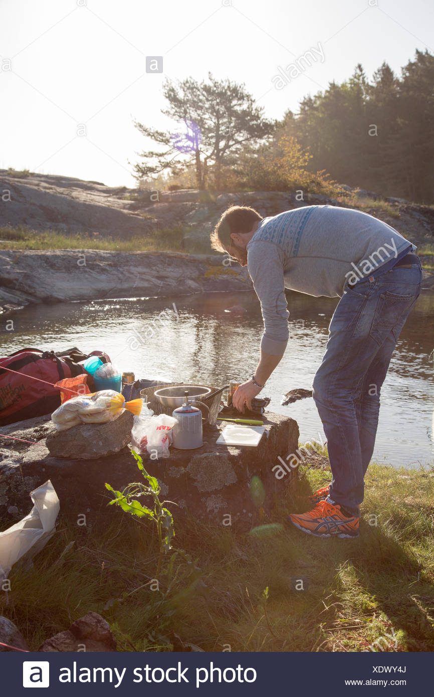 Sweden, West Coast, Bohuslan, Flato, Man camping on riverbank - Stock Image