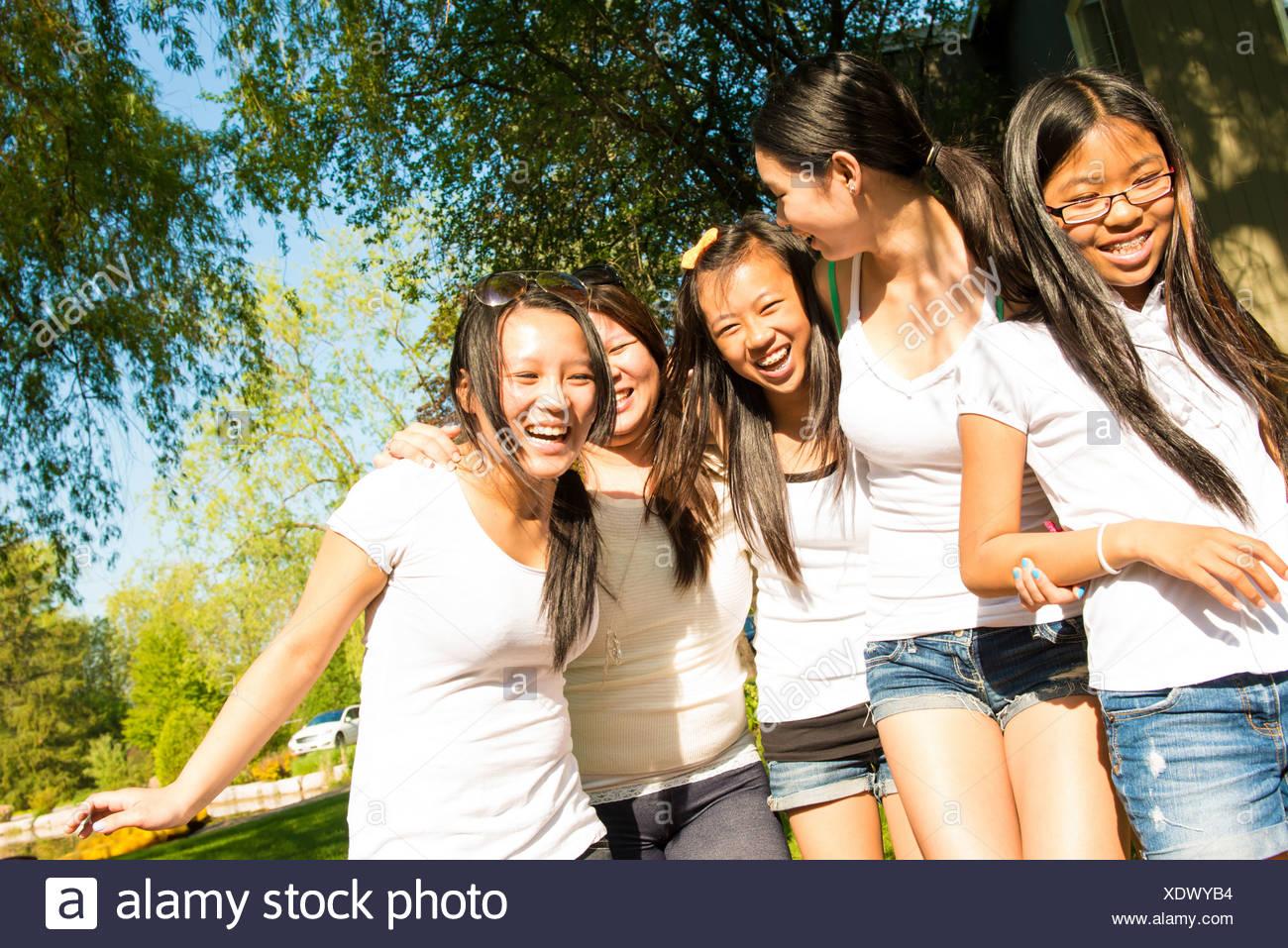 Five girls wearing white t-shirts laughing - Stock Image