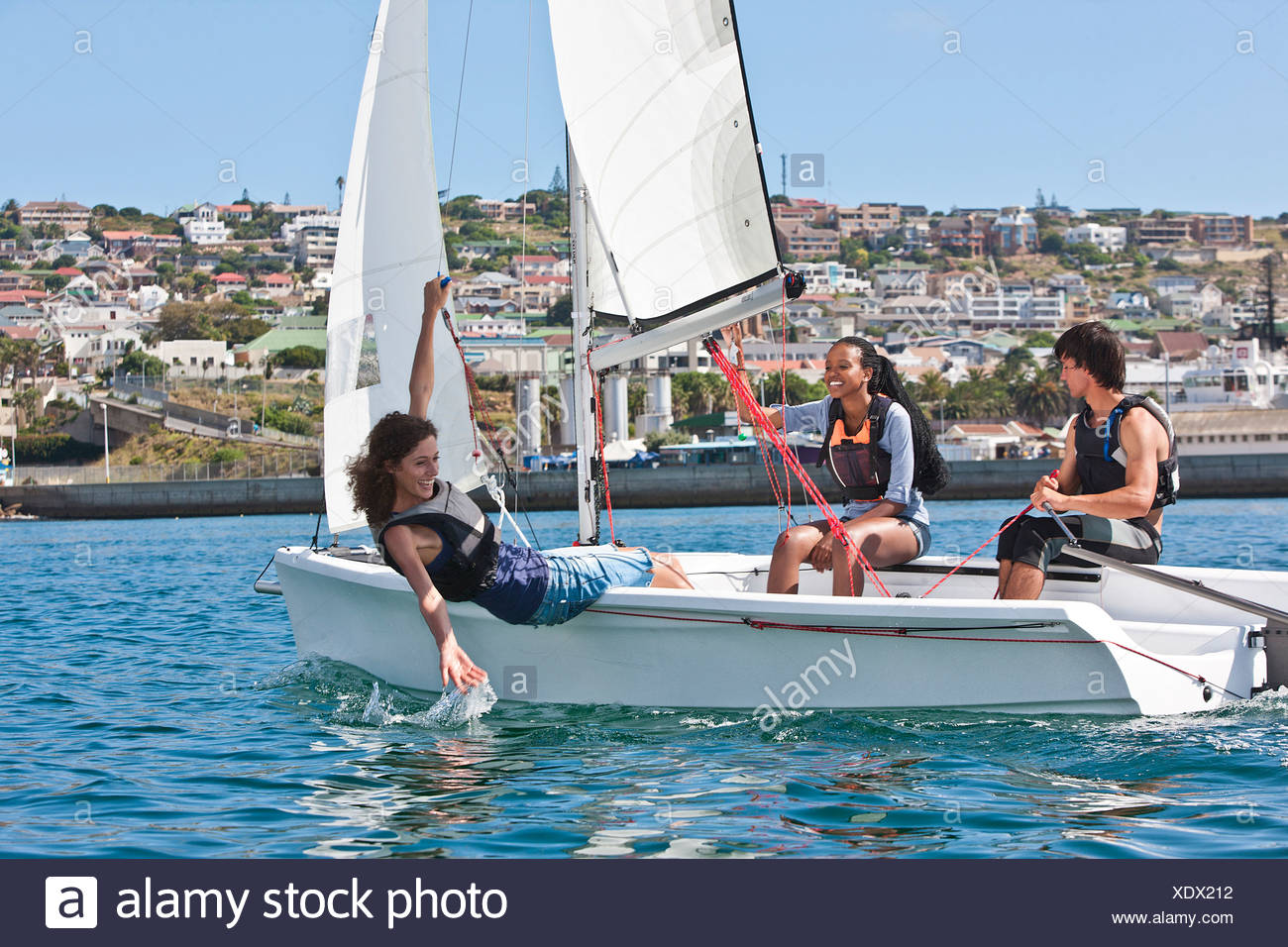 Three young friends sailing in harbor - Stock Image