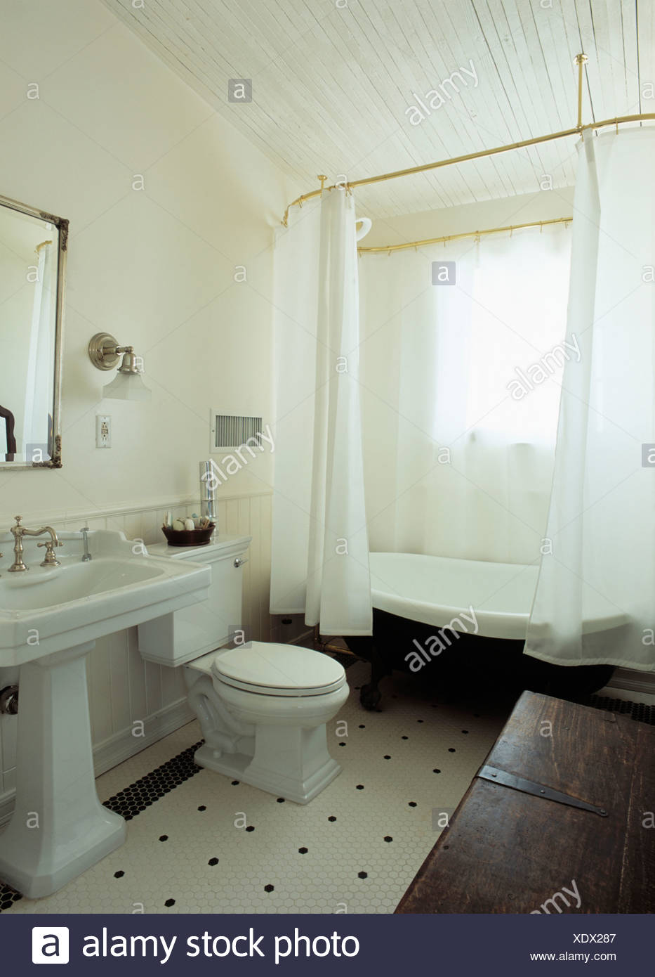 White Shower Curtains On Freestanding Bath In Traditional Bathroom With Pedestal Basin And Black Flooring