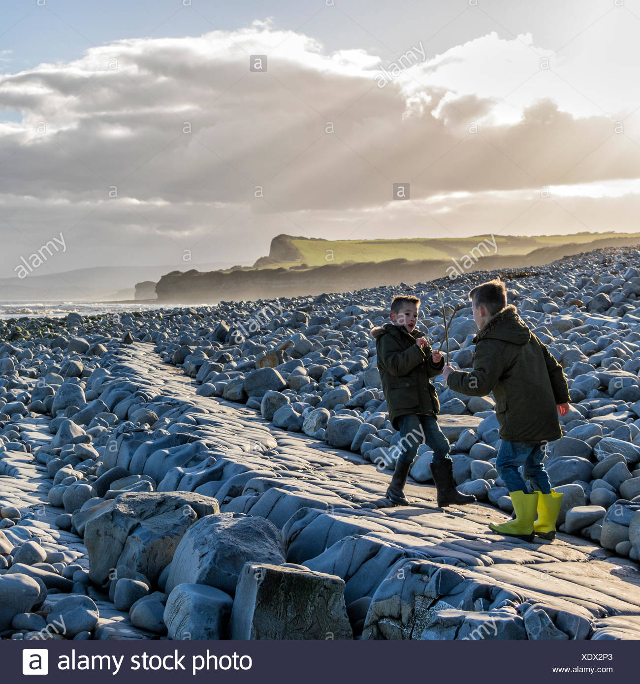 Two boys having a pretend sword fight with sticks on the beach - Stock Image