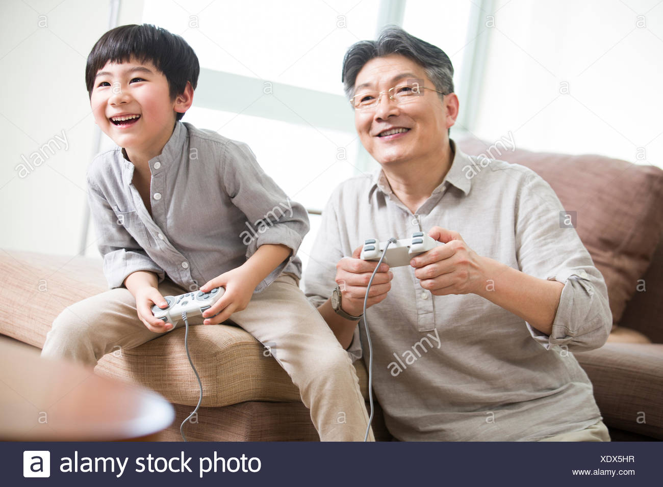 Cheerful grandfather and grandson playing video game Stock Photo