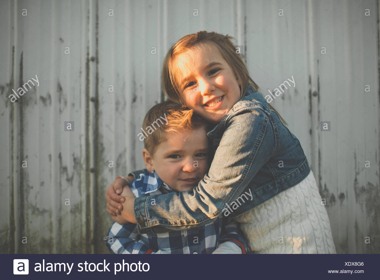 A young girl gives her younger brother a hug. - Stock Image