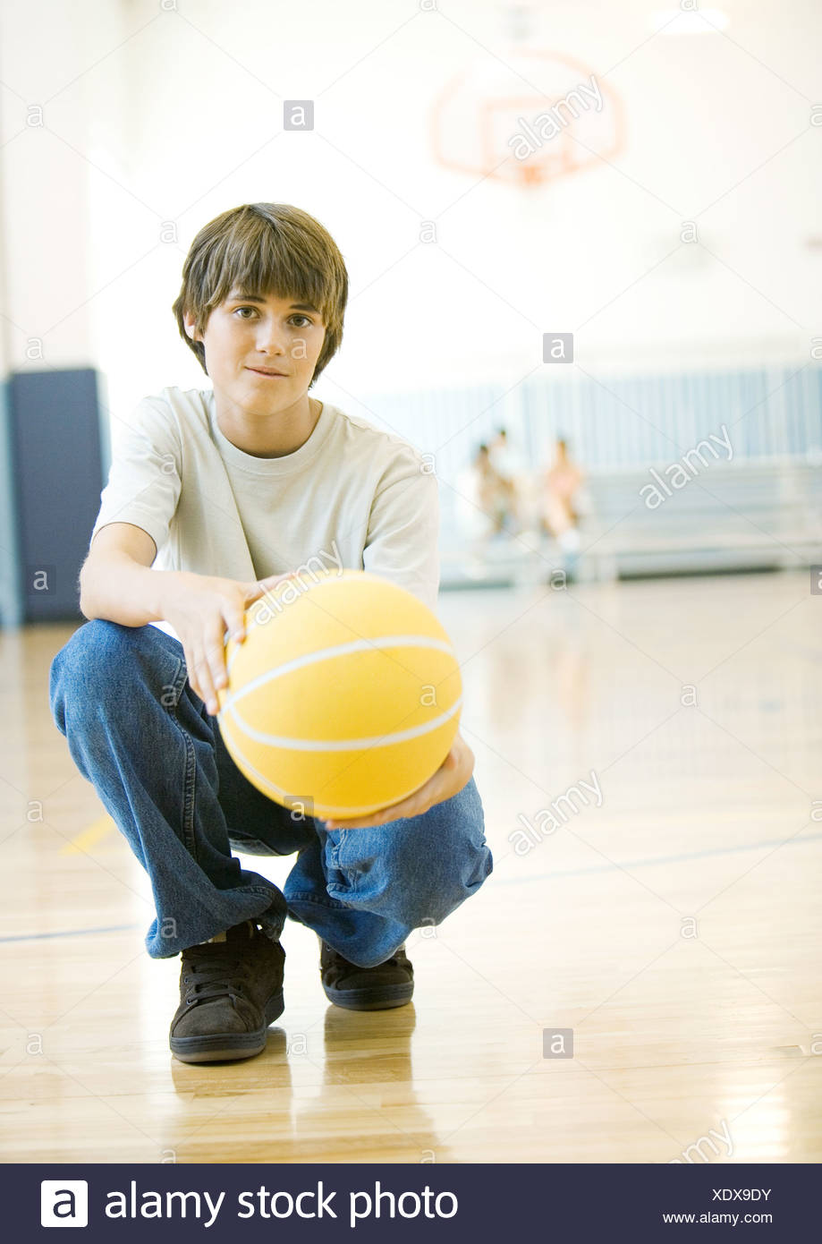 Teen boy crouching with basketball in school gym - Stock Image