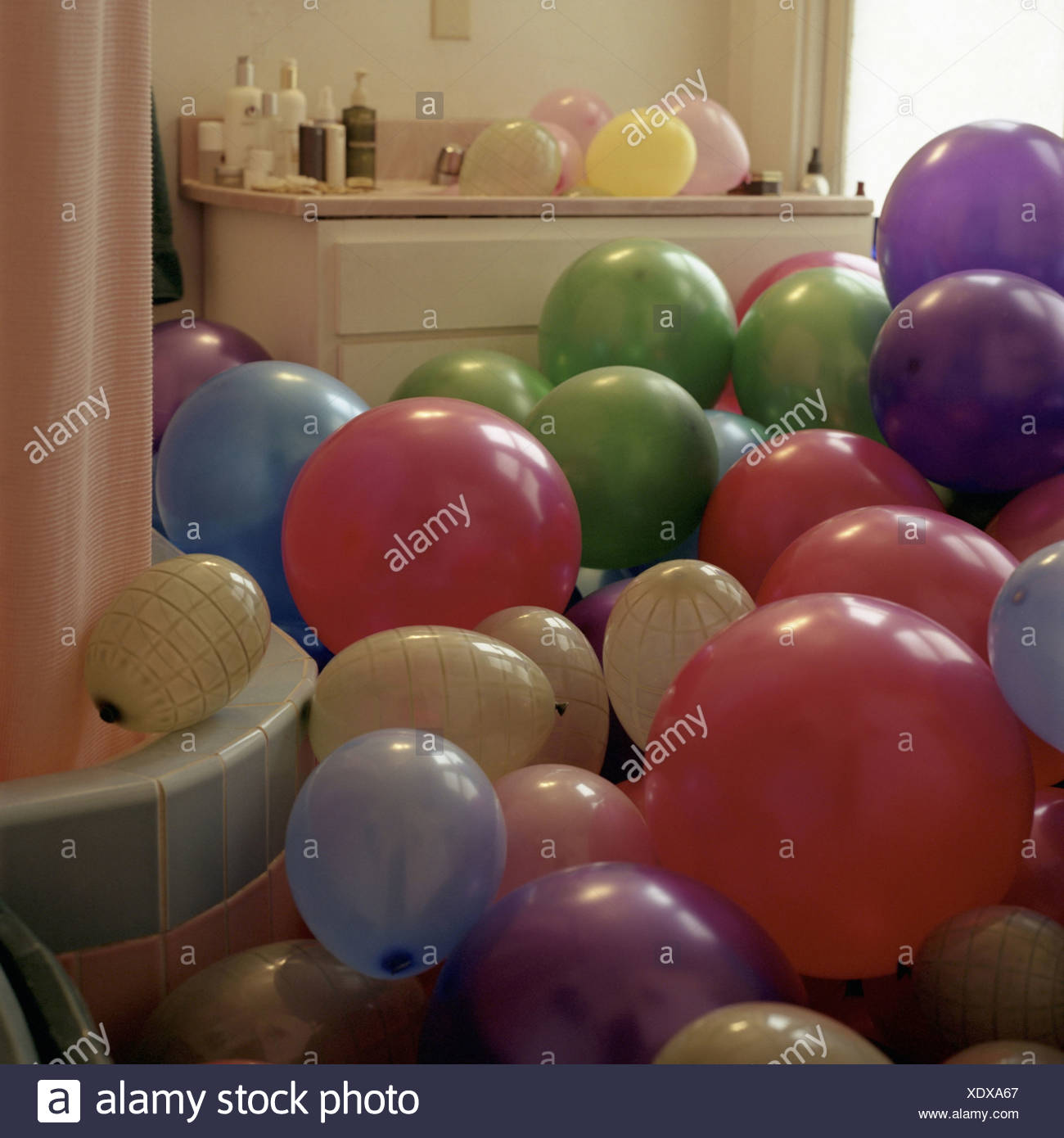 Bathroom balloons prank joke humor overfills cleverly surprise wedding wedding-prank bath balloons inflated colorfully indoors - Stock Image