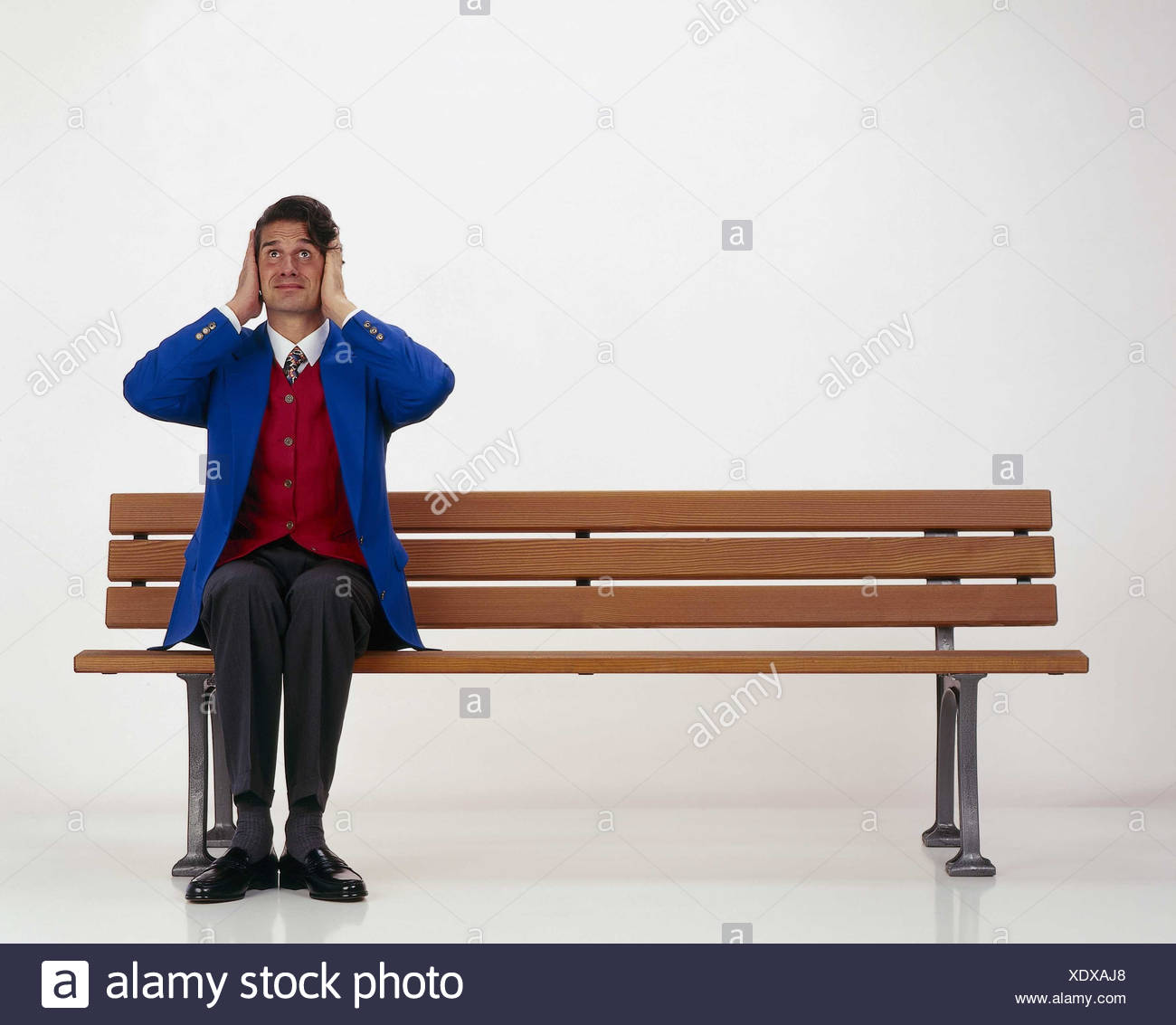 Man, bank, sit, keep closed gesture, ears inside, studio, park-bench, noise, loudly, stress, stressed, overallocated, thrashing, expression - Stock Image