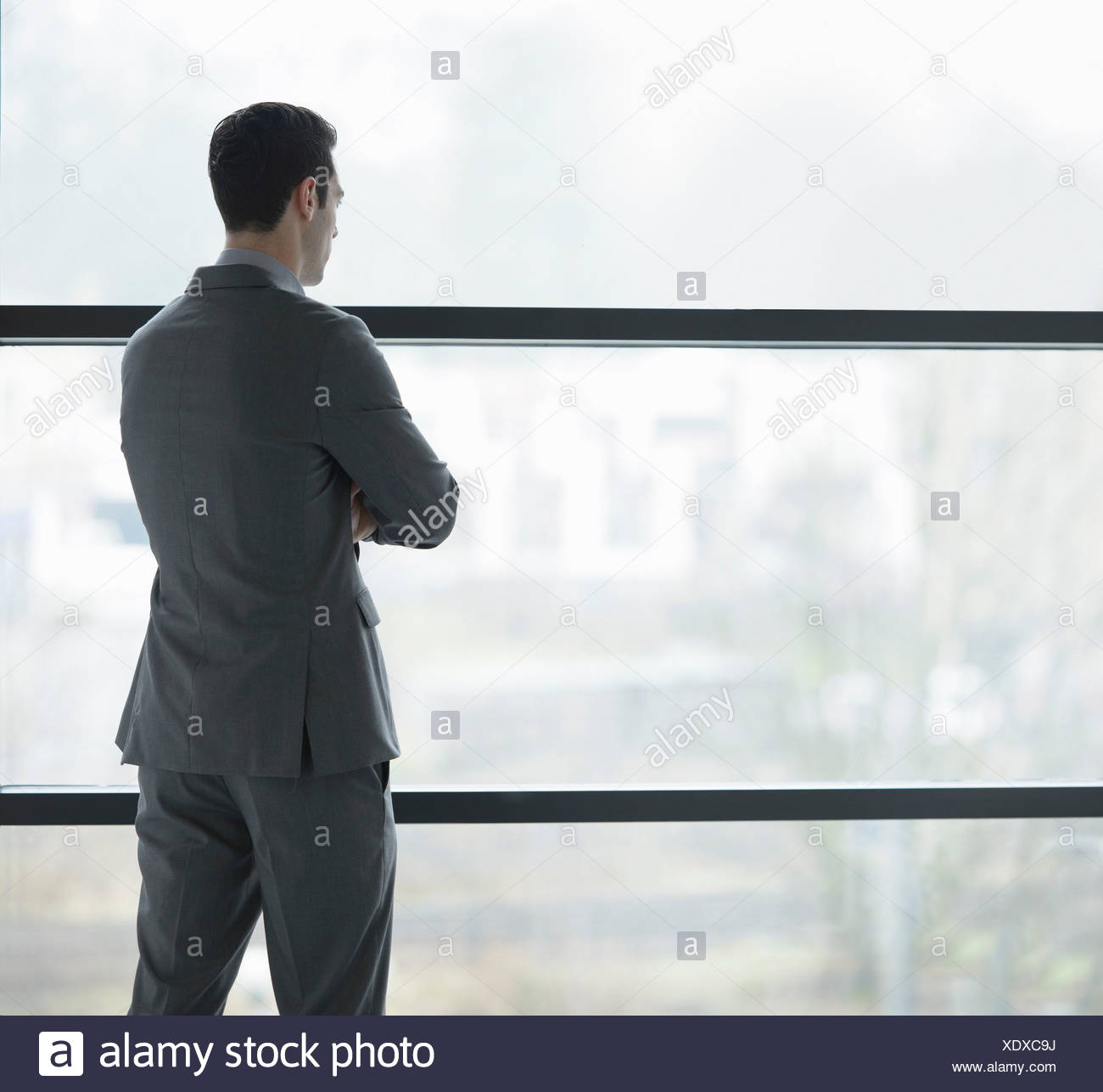 Businessman looking through window - Stock Image