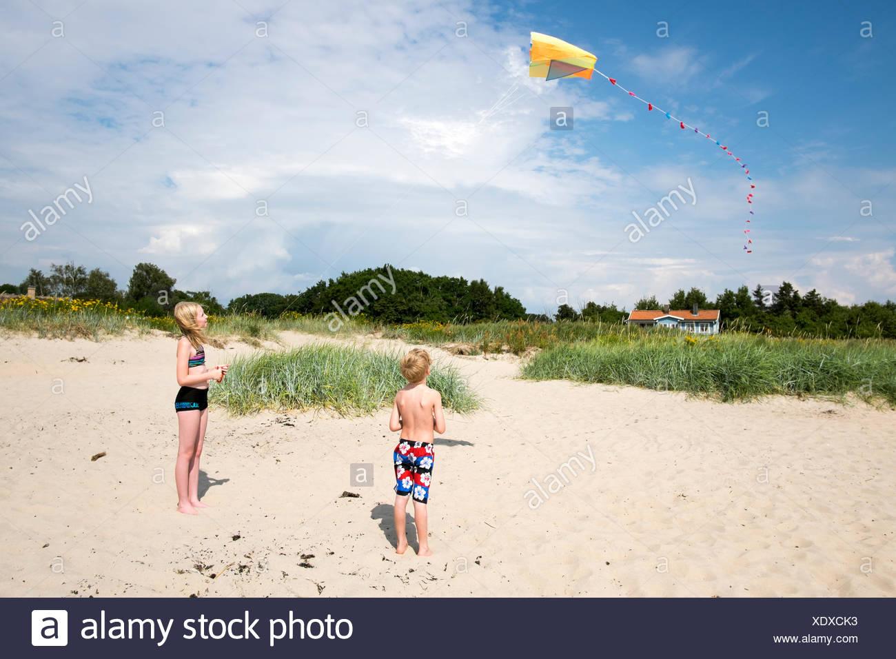 Sweden, Skane, Vejbystrand, Boy (6-7) and girl (10-11) flying kite - Stock Image