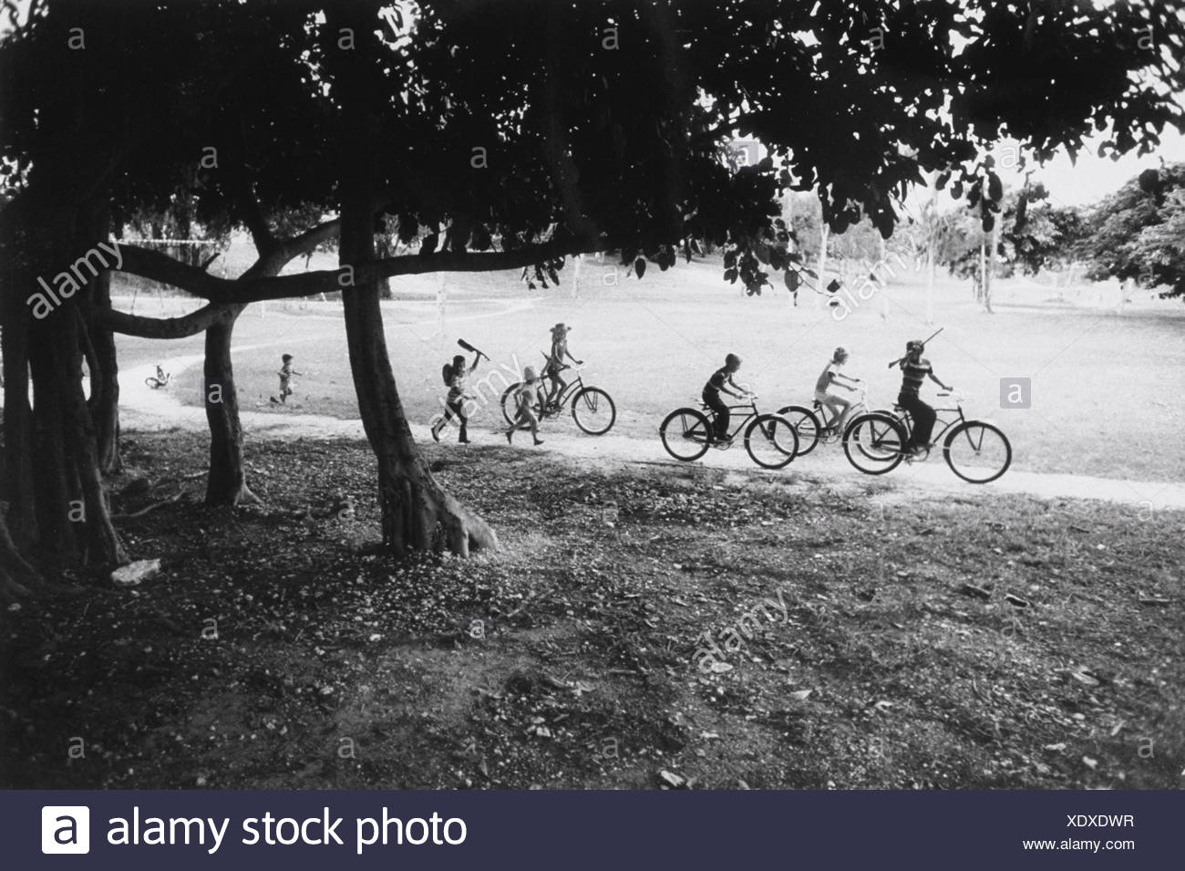 Big brother joins neighborhood boys in male bonding leaves kid sister anxious and fearful deserting her tricycle - Stock Image