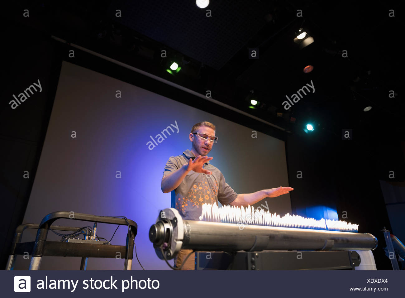 Scientist demonstrating acoustic waves using a Rubens tube in science center theater - Stock Image
