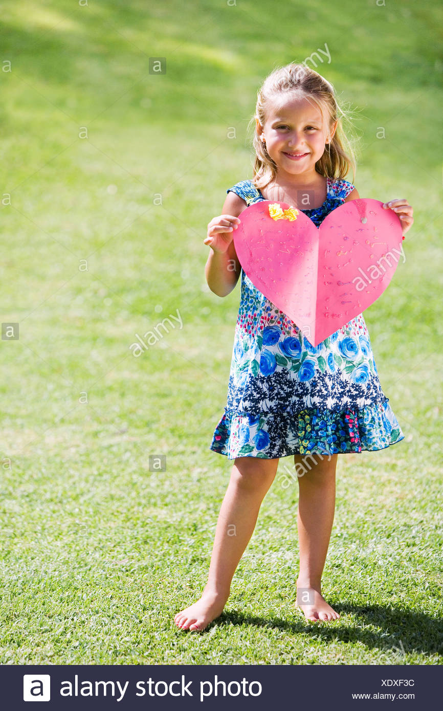 Young girl holding red paper heart - Stock Image