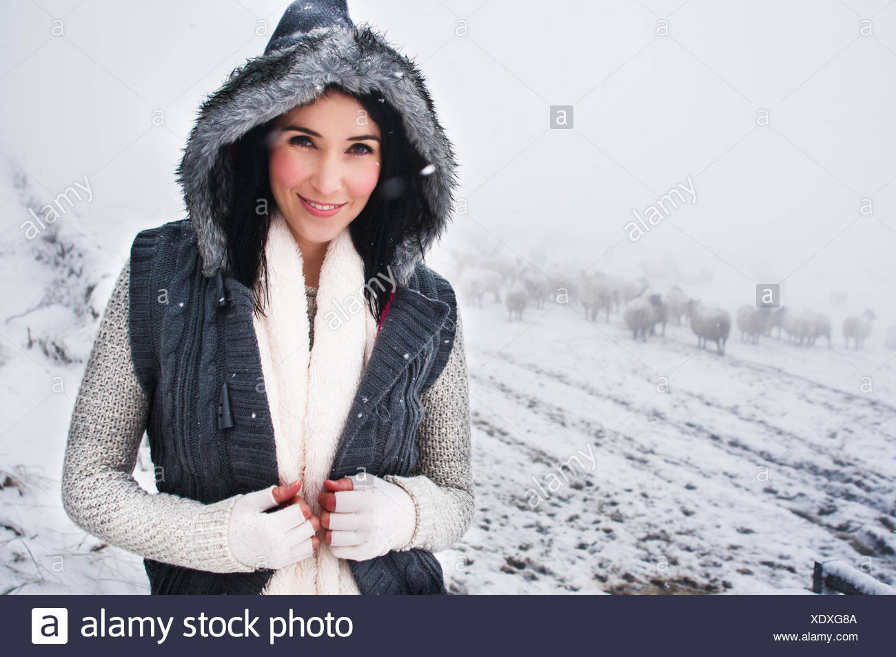 Portrait of smiling woman in snowcapped field - Stock Image