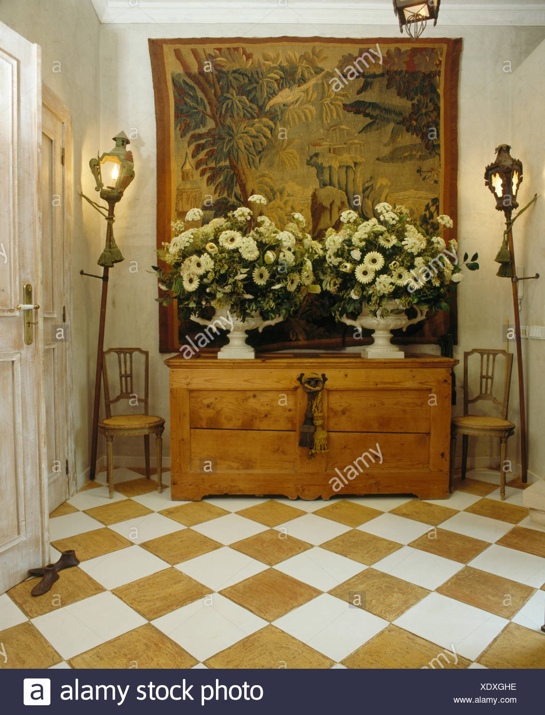 Yellow+white chequerboard floor in hall with tapestry above large floral arrangements on antique pine chest - Stock Image