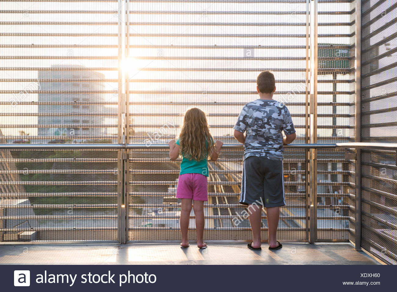 Two children looking down at train tracks at train station - Stock Image