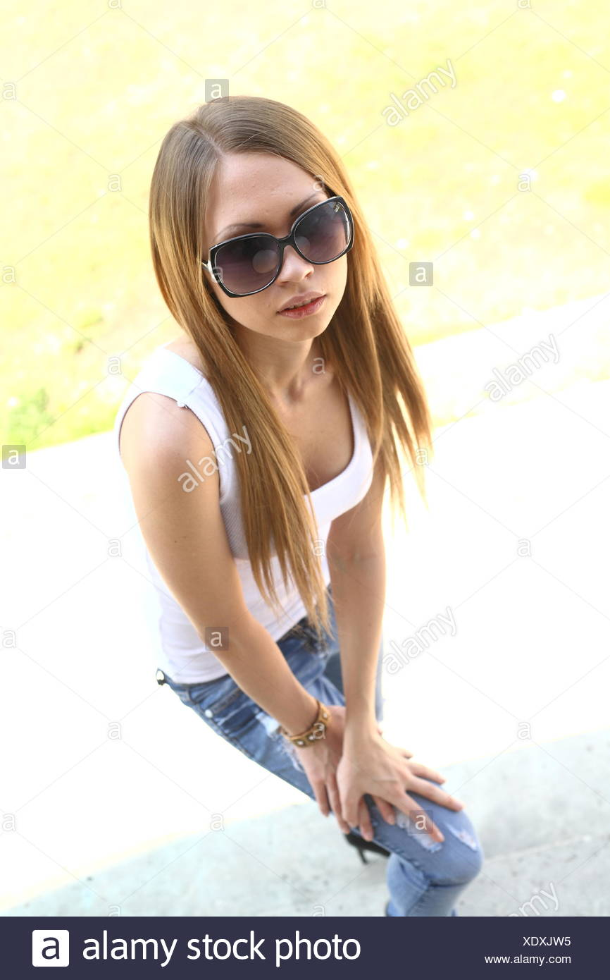 woman in jeans and dark glasses Stock Photo