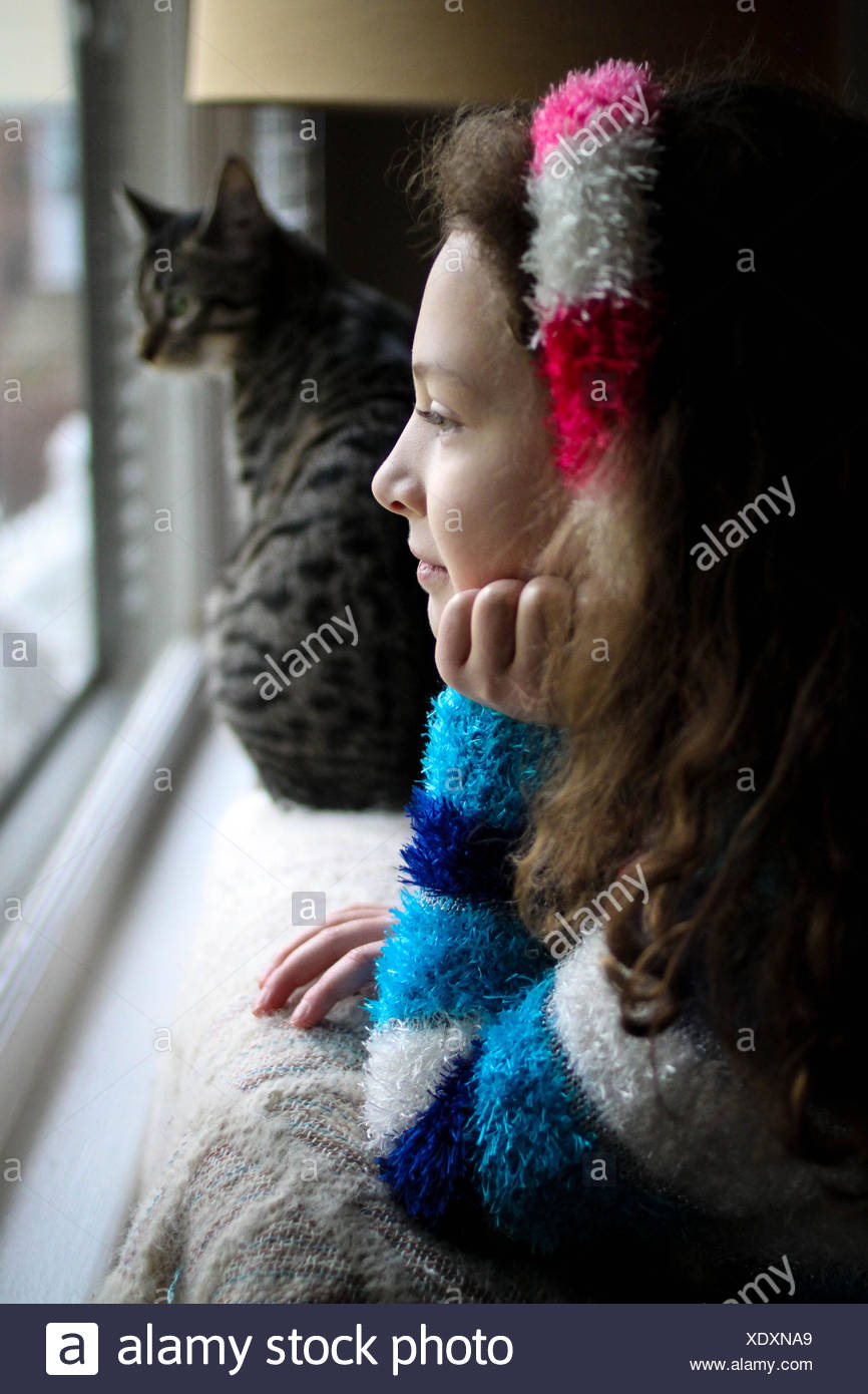 Girl and cat looking out of window - Stock Image