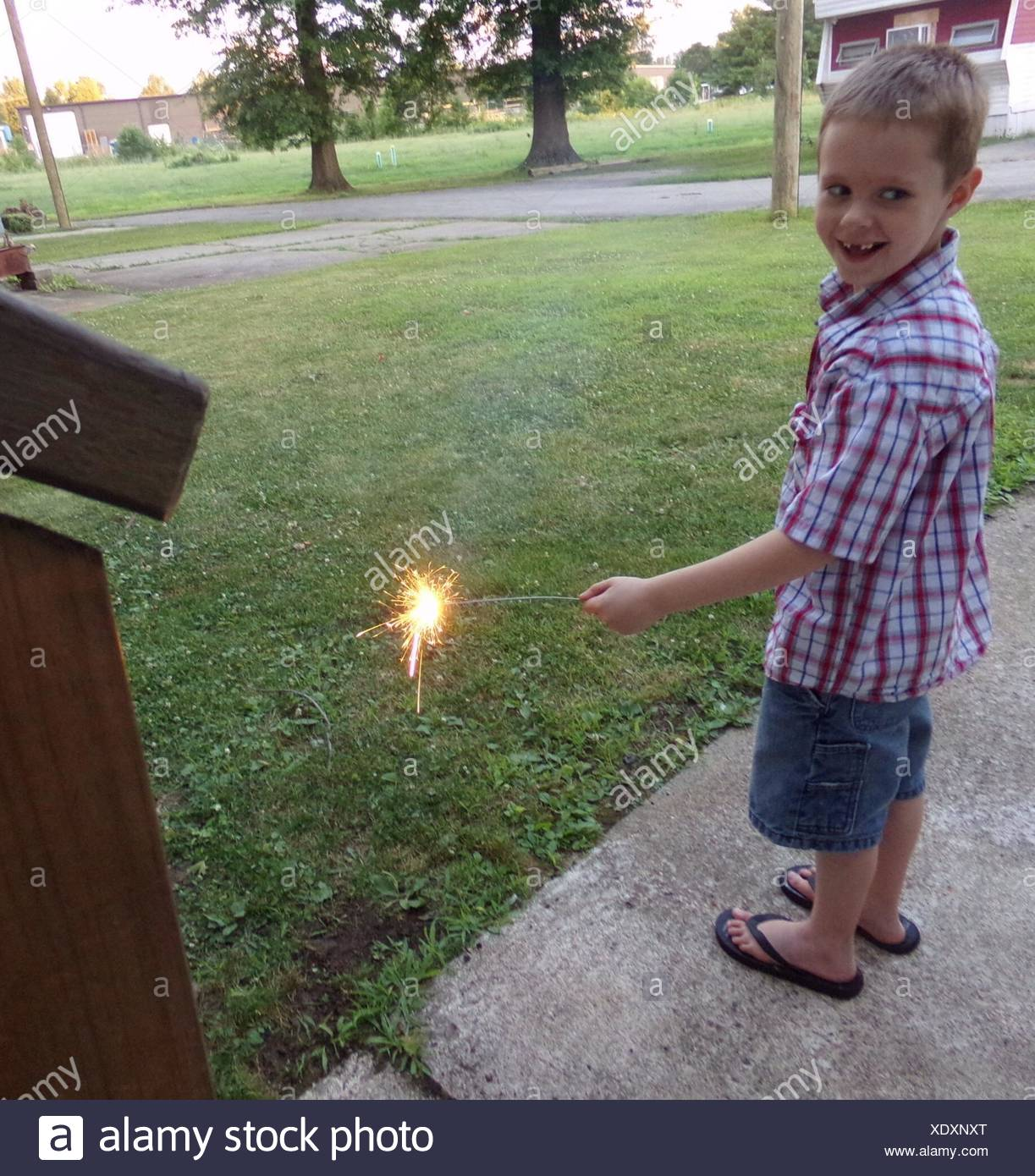Full Length Of Happy Boy Playing With Sparkler In Yard - Stock Image