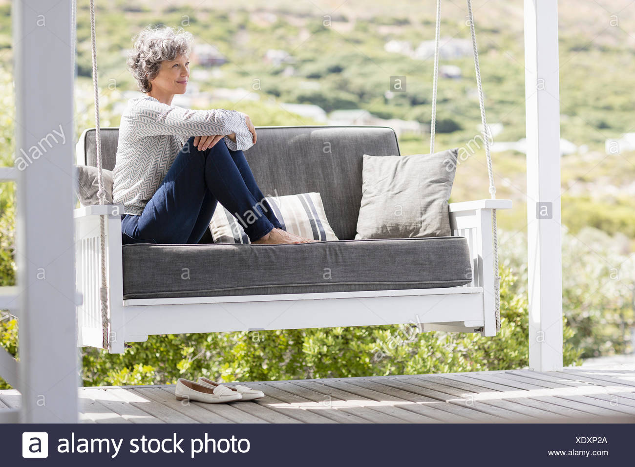 Mature woman sitting on a swing in a porch - Stock Image