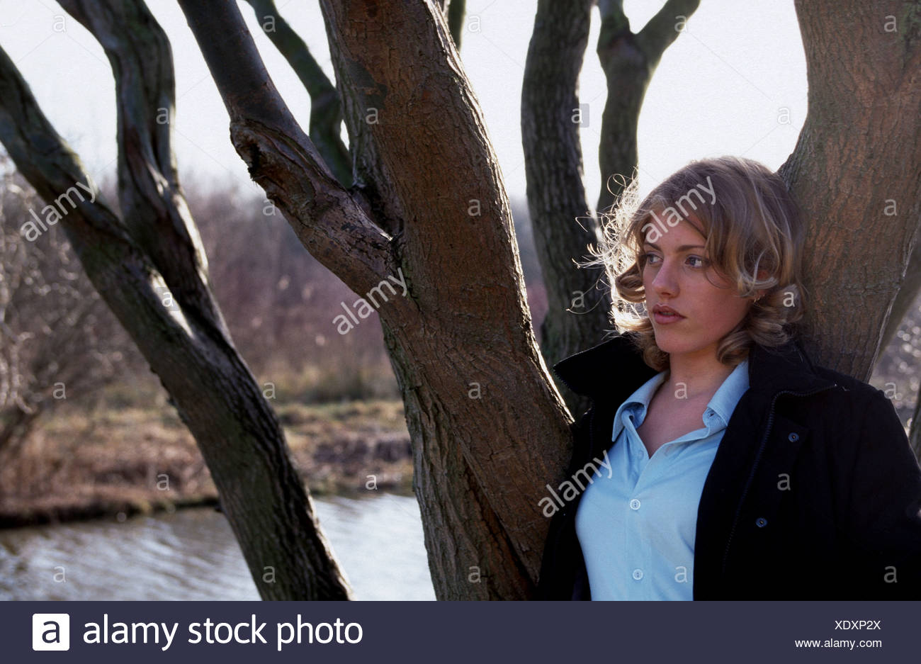 Young sad woman  outside in winter landscape contemplating - Stock Image