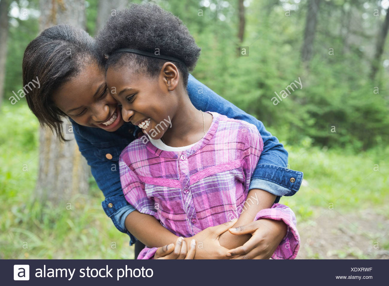 Cheerful sisters hugging outdoors - Stock Image