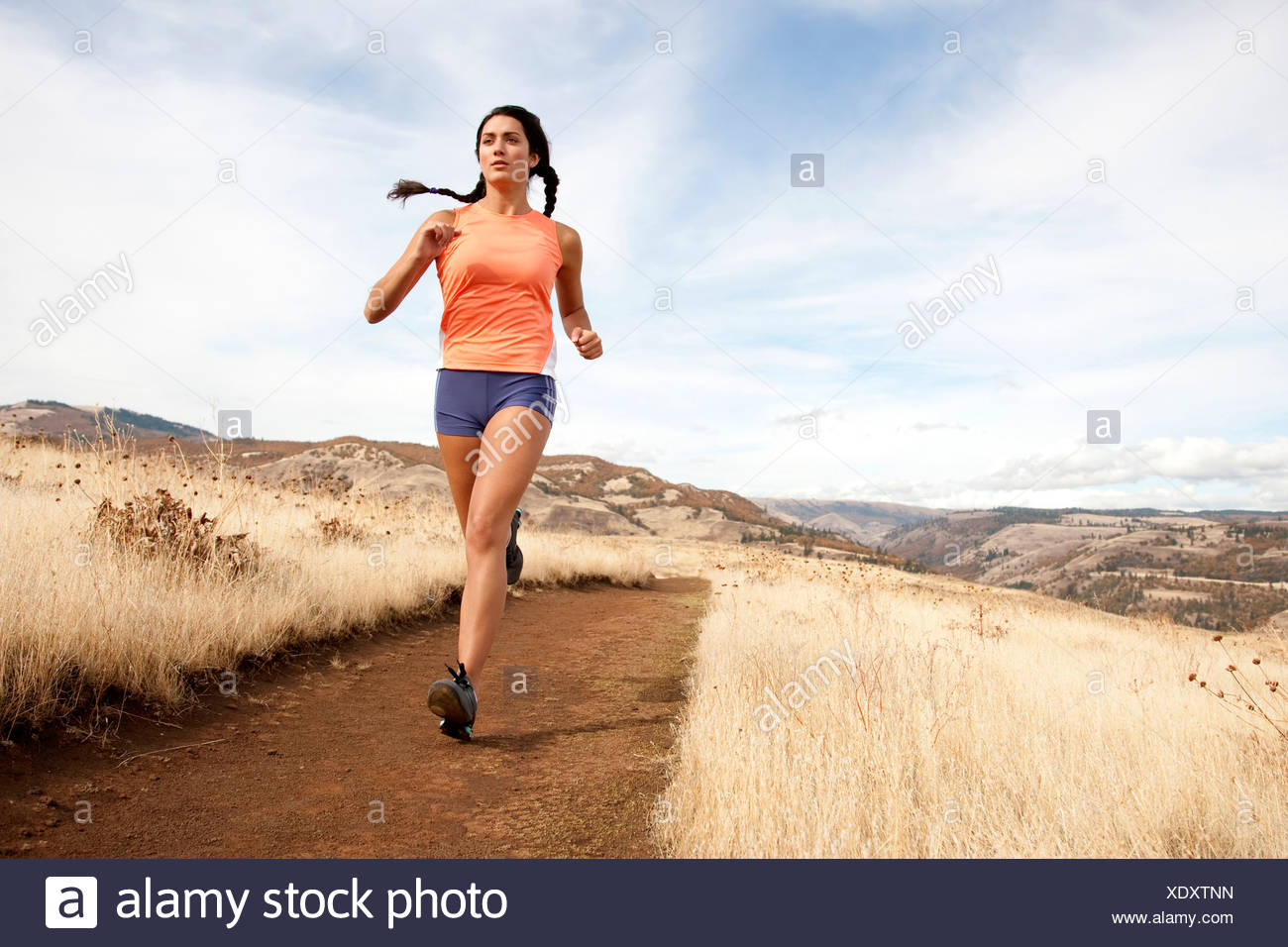 An athletic female jogs on a  dirt trail on an autumn day. - Stock Image