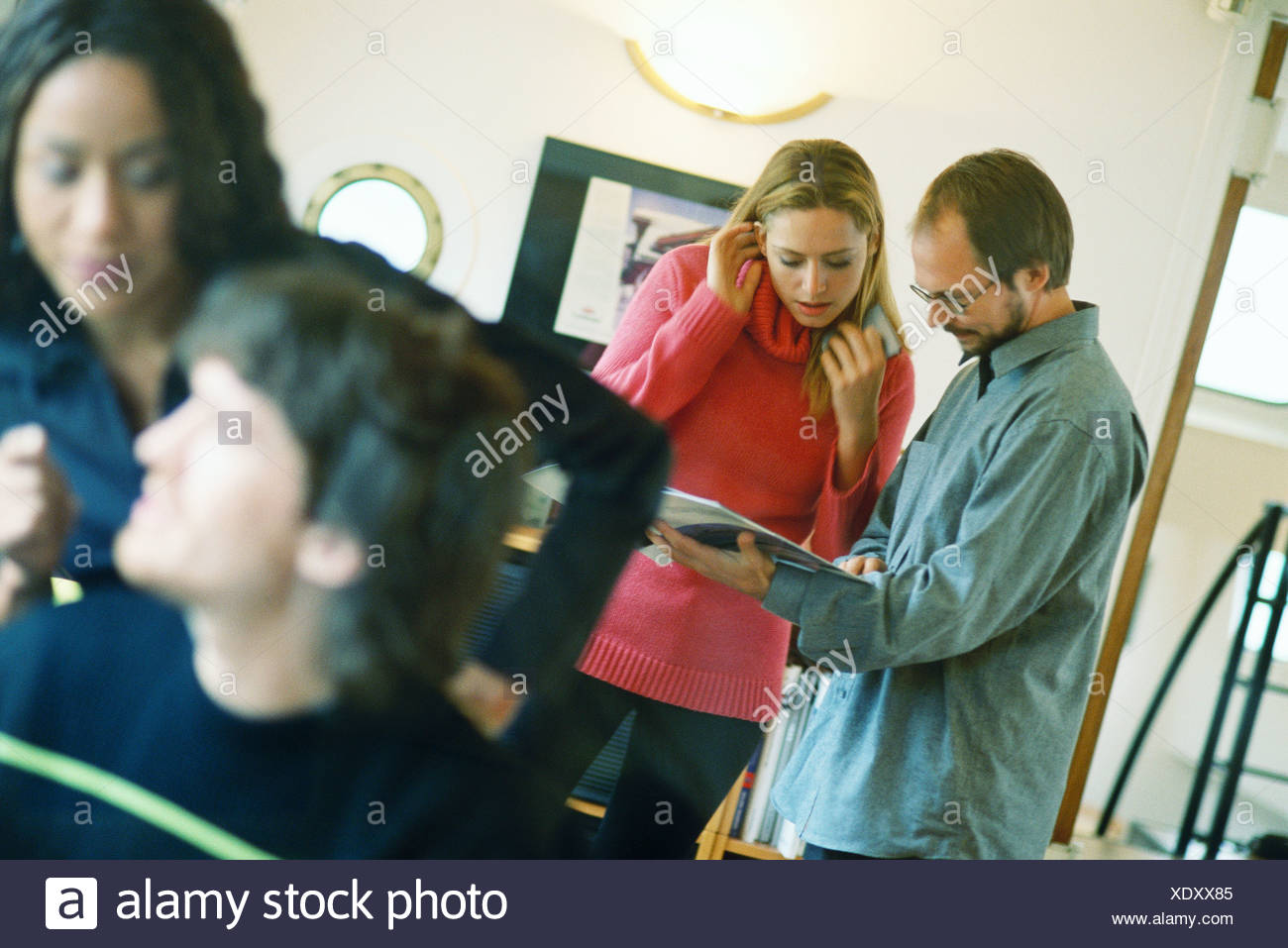 Man and woman looking at catalog, second man and woman in foreground Stock Photo